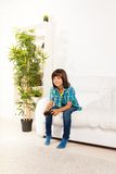 Child play video games. Happy 6 years old boy playing video games holding game controller sitting on the white sofa in living room Stock Photo