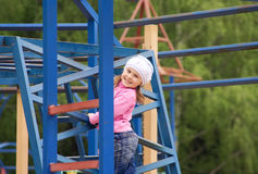 The child on a playgroud. The child stands on high a metal construction Stock Photography
