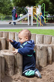 Child at playground. A baby or toddler child playing in a sandpit at public playground; slide other play equipment in the background Royalty Free Stock Photography