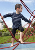 Child at playground. Child playing barefoot at playground on a rope climbing frame equipment Royalty Free Stock Photos