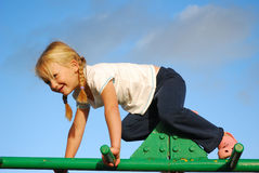 Child on playground. Cute little caucasian girl child playing on a jungle gym at the playground outdoors royalty free stock photo