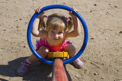 CHILD AT THE PLAYGROUND. Girl playng at the children's playground Stock Photography
