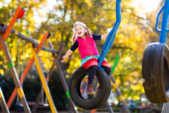 Child on playground in autumn. Kids in fall. Stock Photos