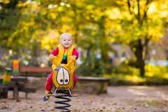 Child on playground in autumn. Kids in fall. Stock Photo