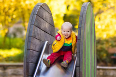 Child on playground in autumn. Kids in fall. Royalty Free Stock Image