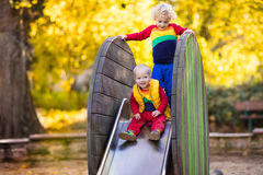 Child on playground in autumn. Kids in fall. Royalty Free Stock Photo