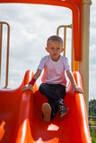 Child in playground boy playing on slide Stock Photography