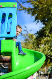 Child on the playground. Cute  fashion smiling boy sat the playground in a sunny day Royalty Free Stock Photo