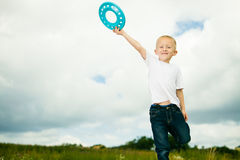 Child in playground kid in action boy playing with frisbee Royalty Free Stock Images