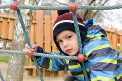 Child at playground park. Child playing at children playground, climbing the  rope ladder frame Stock Images