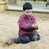 Child at playground playing in sand pit. Child toddler,  playing with sand at public playground in a park Royalty Free Stock Photos