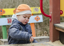 Child at playground playing with sand Stock Images
