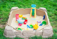 Child playground with Sandbox and toys in a backyard. Of countryside suburb house on a sunny summer day Royalty Free Stock Photography