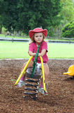 Child on playground seesaw stock image