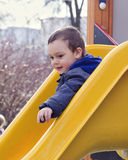 Child on playground slide Stock Image