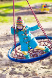 Child on playground swing Royalty Free Stock Images