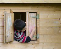 Child in playhouse drawing with chalk royalty free stock photography