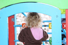 Child playing. A caucasian child with her back towards the camera playing a game at a playground Stock Photo
