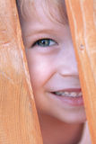Child playing. Kid plays, peeping out of the fence stock photography