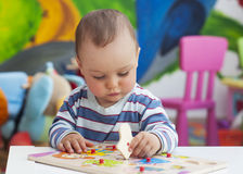 Child playing. Small toddler or a baby child playing with puzzle shapes on a low table in a colorful children room in a nursery or preschool Royalty Free Stock Images