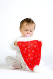 Child playing. A cute toddler girl with a sucker in her mouth playing with a Christmas cap, on a white background Royalty Free Stock Photography