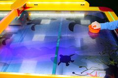 Child is playing air hockey game and holding striker. Mallets and puck in hands. Violet table with pattern. Game in entertainment. Center. Table play. Fun and stock image