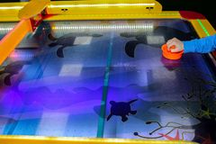 Child is playing air hockey game and holding striker. Mallets and puck in hands. Violet table with pattern. Game in entertainment. Center. Table play. Fun and royalty free stock photos