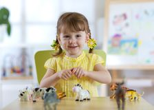 Child playing with animal toys at table in kindergarten or home stock photo