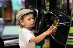Child playing arcade game machine. At an amusement park Royalty Free Stock Photography