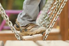 Child playing at the attractions of the swings, legs close-up royalty free stock image