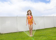Child playing in the backyard sprinklers Stock Photos