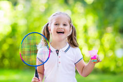 Child playing badminton or tennis outdoor in summer. Active preschool girl playing badminton in outdoor court in summer. Kids play tennis. School sports for Royalty Free Stock Photos