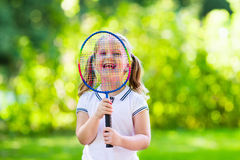 Child playing badminton or tennis outdoor in summer Royalty Free Stock Photography