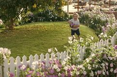 Child is playing ball. Child play with ball on green grass on idyllic day. Summer vacation concept. Kid in garden with blossoming flowers. Happy childhood royalty free stock images