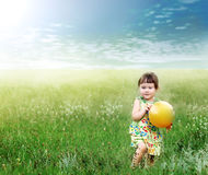 The child playing a ball on the meadow filled Stock Photo