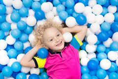 Kids play in ball pit. Child playing in balls pool. Child playing in ball pit. Colorful toys for kids. Kindergarten or preschool play room. Toddler kid at day Royalty Free Stock Image
