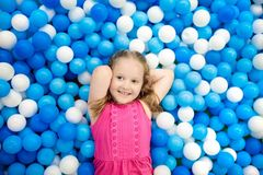 Kids play in ball pit. Child playing in balls pool. Child playing in ball pit. Colorful toys for kids. Kindergarten or preschool play room. Toddler kid at day Stock Photo