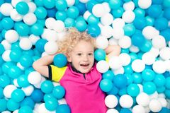 Kids play in ball pit. Child playing in balls pool. Child playing in ball pit. Colorful toys for kids. Kindergarten or preschool play room. Toddler kid at day Royalty Free Stock Photography