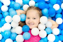 Kids play in ball pit. Child playing in balls pool. Child playing in ball pit. Colorful toys for kids. Kindergarten or preschool play room. Toddler kid at day Stock Photography