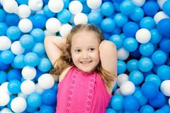 Kids play in ball pit. Child playing in balls pool. Child playing in ball pit. Colorful toys for kids. Kindergarten or preschool play room. Toddler kid at day Stock Images