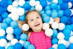 Kids play in ball pit. Child playing in balls pool. Child playing in ball pit. Colorful toys for kids. Kindergarten or preschool play room. Toddler kid at day Royalty Free Stock Photos