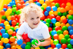 Child playing in ball pit on indoor playground. Happy laughing boy having fun in ball pit on birthday party in kids amusement park and indoor play center. Child Stock Image