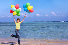 Child playing with balloons at the beach Stock Images