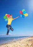 Child playing with balloons at the beach Royalty Free Stock Photo