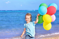 Child playing with balloons at the beach Stock Photography