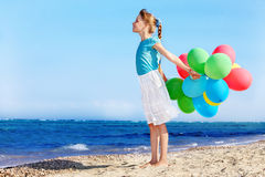 Child playing with balloons at the beach stock photo
