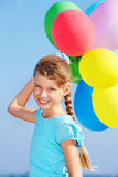 Child playing with balloons at the beach Stock Image