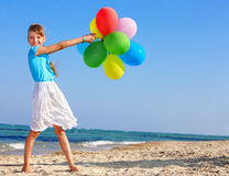 Child playing with balloons at the beach Royalty Free Stock Photography