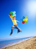 Child playing with balloons at the beach Stock Photos