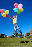 Child playing with balloons in park. Royalty Free Stock Image